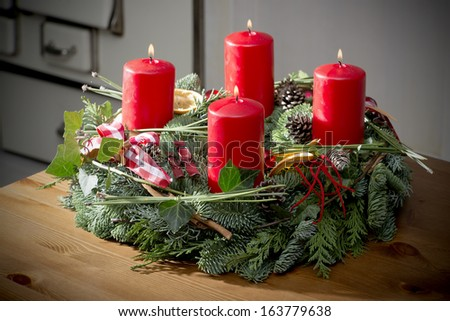 Advent wreath of twigs with four burning red candles and various ornaments - stock photo