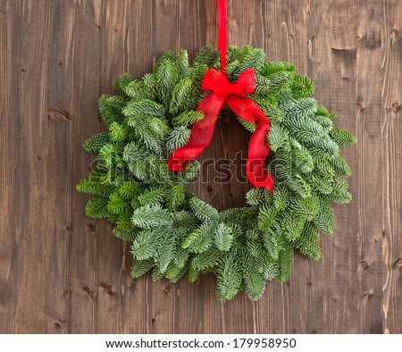 Advent wreath with red ribbon over a brown wooden plank