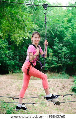 adventure climbing high wire park - hiking in the rope park girl in safety equipment