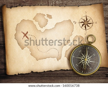 Adventure concept. Old compass on table with treasure map. - stock photo