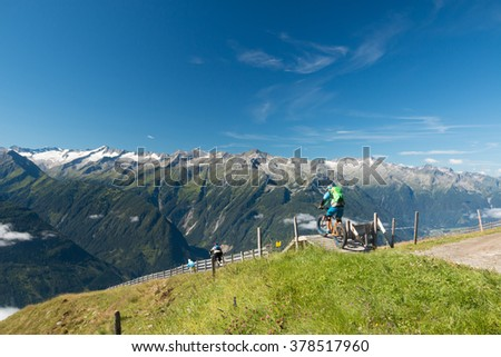 adventure enduro mountain biker riding on a high mountain trail with view in the austrian alps on wildkogel near kaprun in salzburg - stock photo