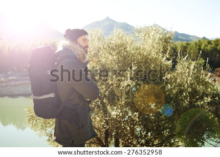Adventure hiking man with backpack.  Hikers walking in mountain forest during camping travel hike. Bearded caucasian male hiker in nature standing.  - stock photo