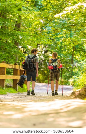 Adventure, tourism active lifestyle- young couple backpacker hiking in forest pathway back view - stock photo