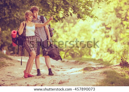 Adventure, tourism, enjoying summer time together - Hiking young couple with guitar backpack tramping on forest road sunny countryside