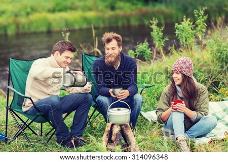 adventure, travel, tourism and people concept - group of smiling friends cooking food in dixie sitting around bonfire outdoors - stock photo