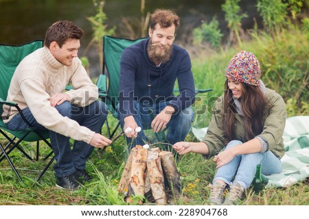 adventure, travel, tourism and people concept - group of smiling friends with marshmallow sitting around bonfire in camping - stock photo