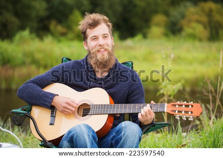 adventure, travel, tourism and people concept - smiling man with guitar and cooking food on bonfire in camping - stock photo