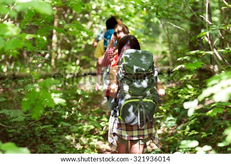 adventure, travel, tourism, hike and people concept - close up of friends walking with backpacks in woods from back - stock photo