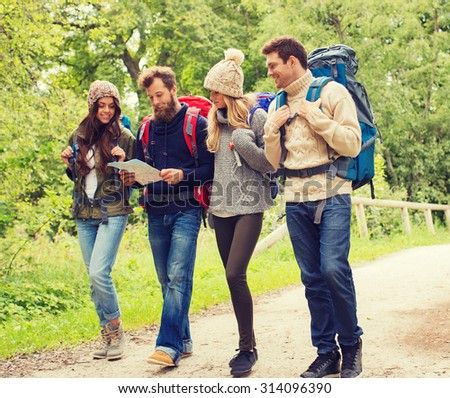 adventure, travel, tourism, hike and people concept - group of smiling friends walking with backpacks and map walking outdoors - stock photo