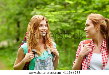 adventure, travel, tourism, hike and people concept - group of smiling friends walking with backpacks in woods - stock photo