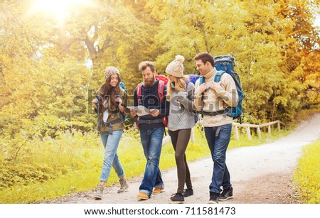 adventure, travel, tourism, hike and people concept - group of smiling friends walking with backpacks and map walking in autumn forest