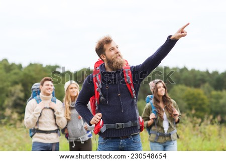 adventure, travel, tourism, hike and people concept - group of smiling friends with backpacks pointing finger outdoors