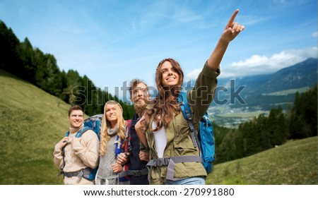 adventure, travel, tourism, hike and people concept - group of smiling friends with backpacks pointing finger over alpine hills background - stock photo