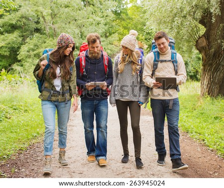 adventure, travel, tourism, hike and people concept - group of smiling friends with backpacks and tablet pc computer walking outdoors - stock photo
