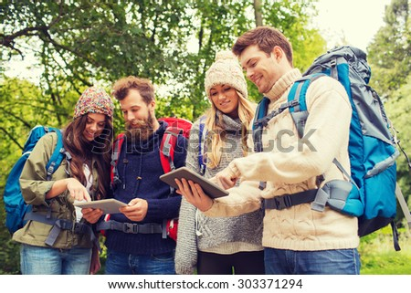 adventure, travel, tourism, hike and people concept - group of smiling friends with backpacks and tablet pc computers outdoors