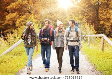 adventure, travel, tourism, hike and people concept - group of smiling friends with backpacks and tablet pc computer walking in autumn forest