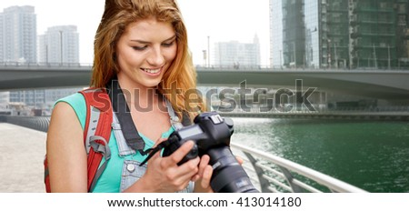 adventure, travel, tourism, hike and people concept - happy young woman with backpack and camera photographing over dubai city waterfront and bridge background - stock photo