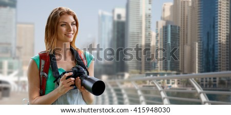 adventure, travel, tourism, hike and people concept - happy young woman with backpack and camera photographing over dubai city waterfront background - stock photo