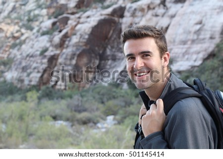 Adventure, travel, tourism, hike and people concept - man carrying black backpack hiking in the desert rocky mountains