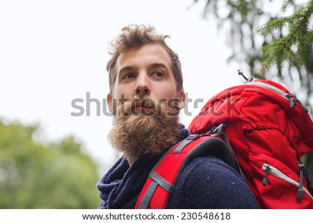 adventure, travel, tourism, hike and people concept - man with beard and red backpack hiking - stock photo