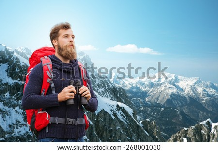 adventure, travel, tourism, hike and people concept - man with red backpack and binocular over alpine mountains background - stock photo
