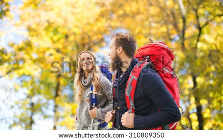 adventure, travel, tourism, hike and people concept - smiling couple walking with backpacks over natural background - stock photo