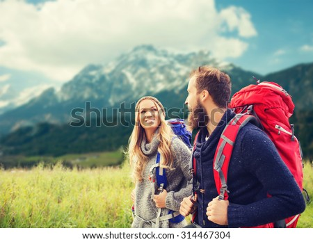 adventure, travel, tourism, hike and people concept - smiling couple walking with backpacks over alpine mountains background - stock photo