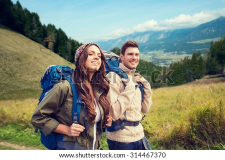 adventure, travel, tourism, hike and people concept - smiling couple walking with backpacks over alpine hills background - stock photo