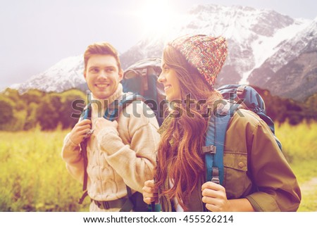 adventure, travel, tourism, hike and people concept - smiling couple walking with backpacks over alpine mountains and hills background - stock photo