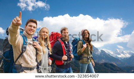 adventure, travel, tourism, hike and people concept - smiling friends walking with backpacks and pointing finger to something over mountains background