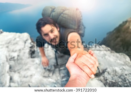 adventurers helping each other to climb the mountain - stock photo