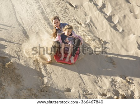 Adventuresome girls boarding down the Sand Dunes - stock photo