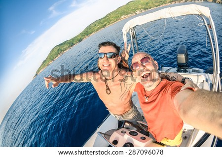 Adventurous best friends taking selfie at Giglio Island on luxury speedboat - Adventure travel lifestyle enjoying happy fun moment - Trip together around the world beauties - Fisheye lens distortion - stock photo