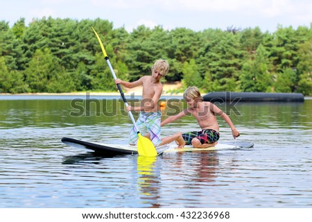 Adventurous boys learning to paddle on stand up board. Happy children, teenage schoolboys, having fun enjoying adventure experience on the river or lake on a sunny day during summer holidays - stock photo