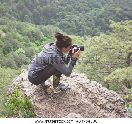 Adventurous female photographer sitting on the rock while photographing mountains. - stock photo