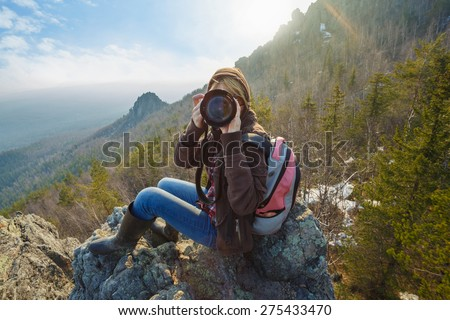 Adventurous female photographer sitting on the rock while photographing mountains facing the camera against setting sun. Wide angle perspective. Tourism, adventure, hiking concept. - stock photo