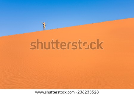 Adventurous man lonely traveler hiking on sand dune at Deadvlei near Sossusvlei - Namibian world famous desert - Adventure trip to african nature wonder shooting travel photography - stock photo