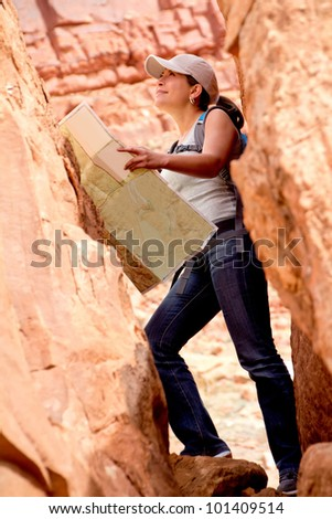 Adventurous woman exploring the desert holding a map - stock photo