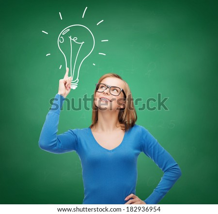 advertisement and electricity concept - attractive young woman in casual clothes and eyeglasses pointing her finger up to light bulb doodle