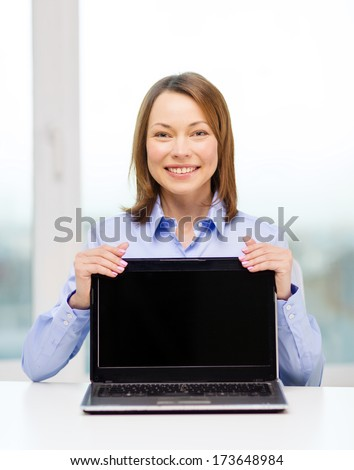 advertisement, business and technology concept - smiling businesswoman with blank black laptop screen - stock photo