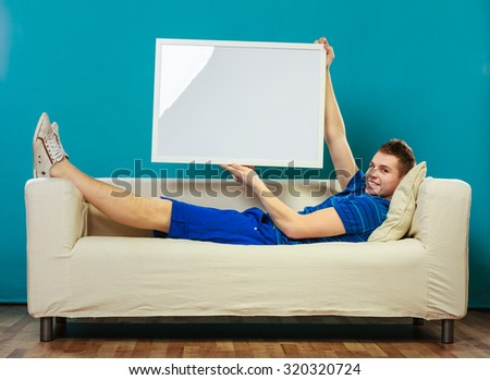 Advertisement concept. Young man laying on sofa with blank presentation board. Male model showing banner sign billboard copy space for text on blue - stock photo