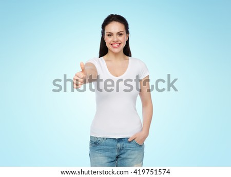 advertisement, gesture, clothing and people concept - happy smiling young woman or teenage girl in white t-shirt showing thumbs up over blue background - stock photo