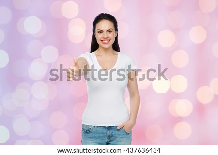 advertisement, gesture, clothing and people concept - happy smiling young woman or teenage girl in white t-shirt showing thumbs up over rose quartz and serenity holidays lights background - stock photo