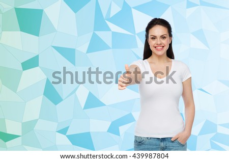advertisement, gesture, clothing and people concept - happy smiling young woman or teenage girl in white t-shirt showing thumbs up over blue low poly background - stock photo