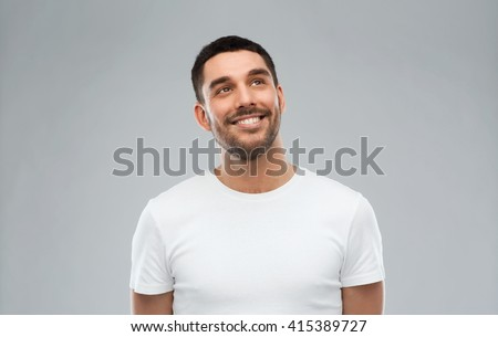 advertisement, idea, inspiration and people concept - happy smiling young man looking up over gray