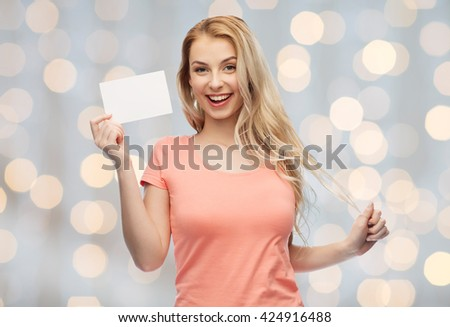 advertisement, invitation, message and people concept - smiling young woman or teenage girl with blank white paper card over holidays lights background - stock photo