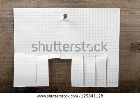advertisement paper with cut slips hanging on nail - stock photo