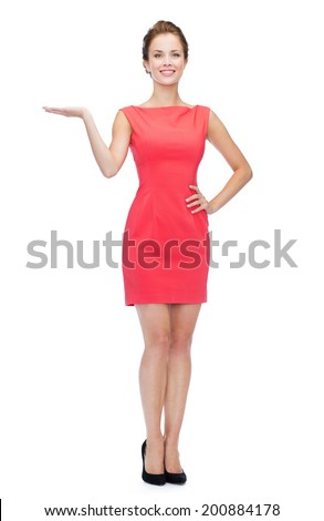 advertising and people concept - smiling young woman in red dress holding something on palm of her hand - stock photo