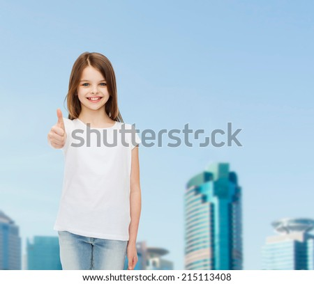 advertising, childhood, city, gesture and people concept - smiling girl in white t-shirt showing thumbs up over business center background - stock photo