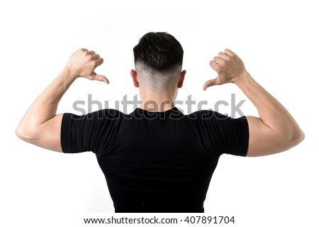 advertising corporate back portrait of young attractive sport man with big strong body pointing with his finger on his black t-shirt with copy space for adding gym and fitness health club logo  - stock photo